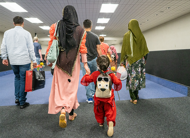 Mother and child holding hands and walking through an airport.