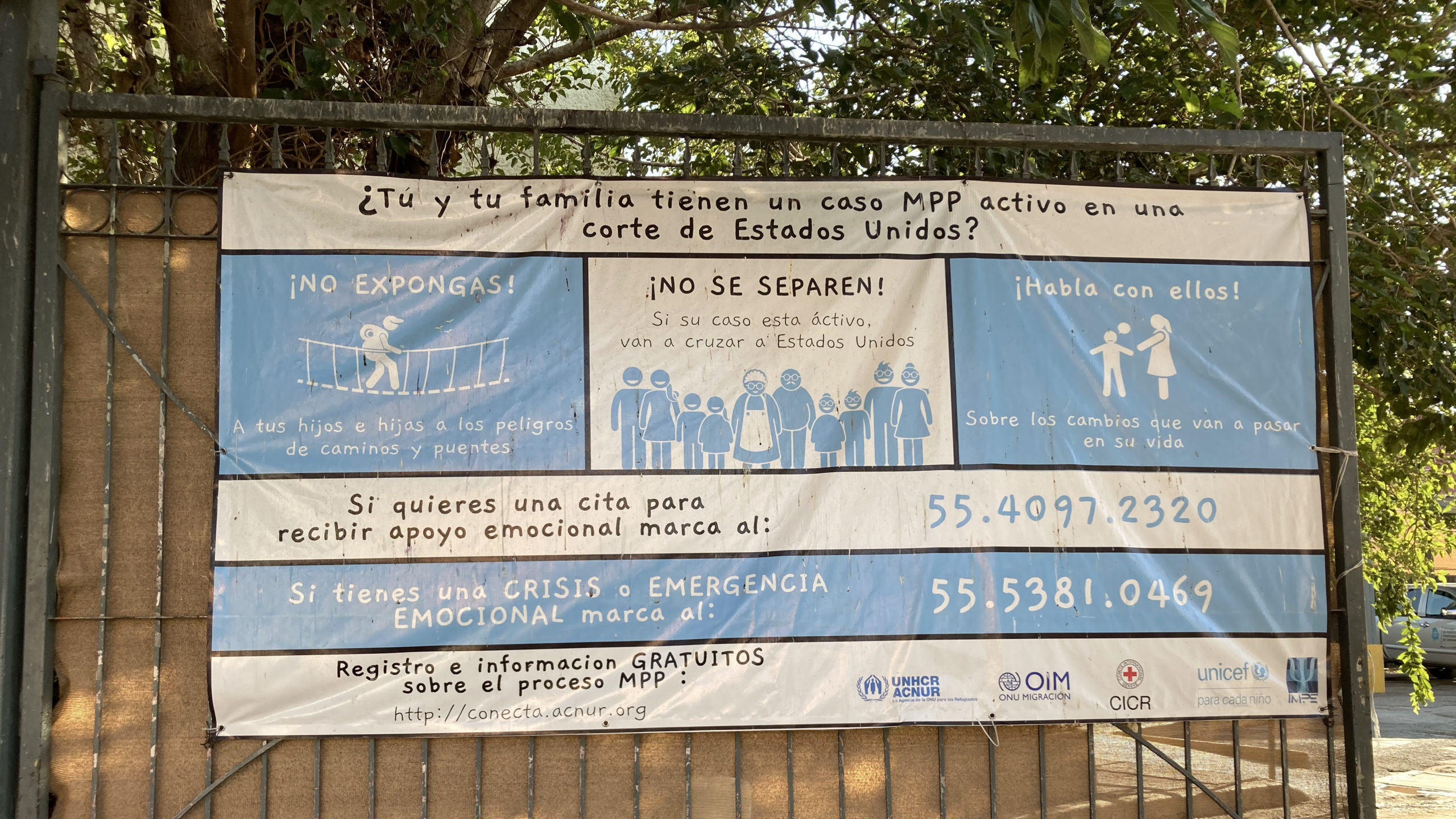 A photo of a white and light blue banner with information from UNHCR for asylum seekers with Migration Protections Protocol (MPP) cases.