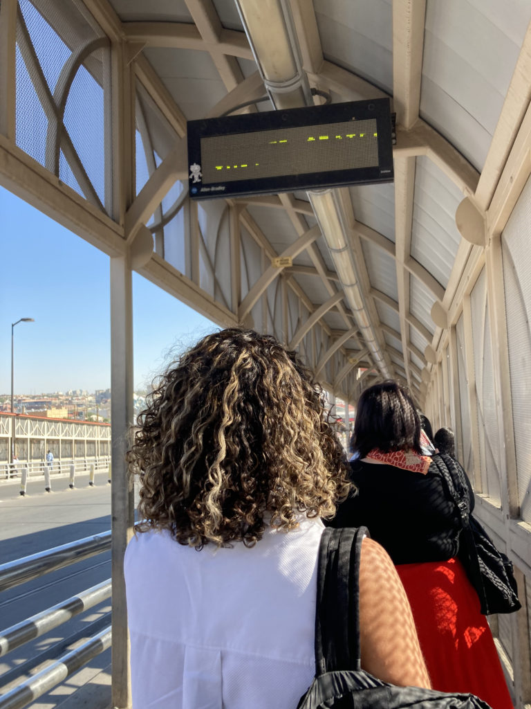 A photo of two IRAP staff members from behind walking along the Paso del Norte border bridge.