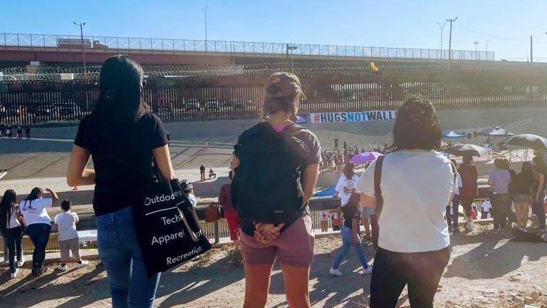 A photo of three IRAP staff members from behind as they look out on families and community members gathered on either side of the border wall.
