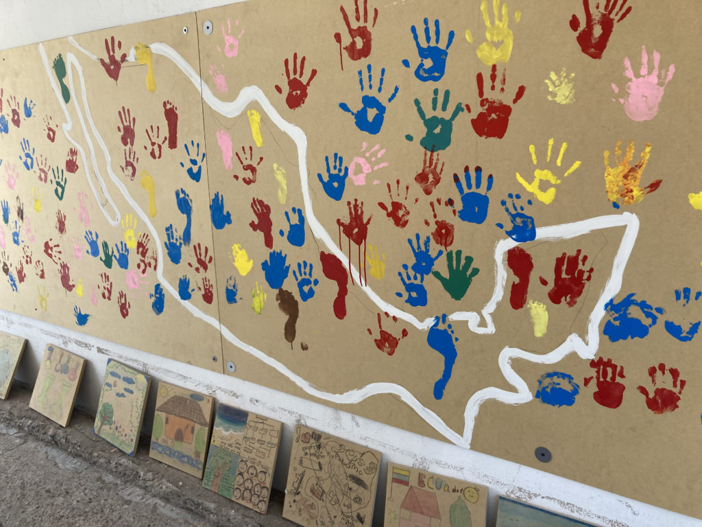 A photo of a mural with a white outline of Mexico and colorful children's handprints, as well as more artwork by children leaned against a wall.